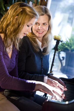 Portrait of mother and teen daughter sitting at grand piano photo