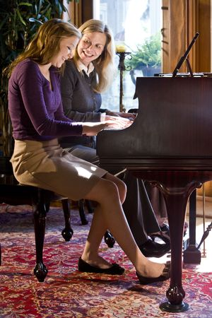 Mother and daughter playing duet on a grand piano
