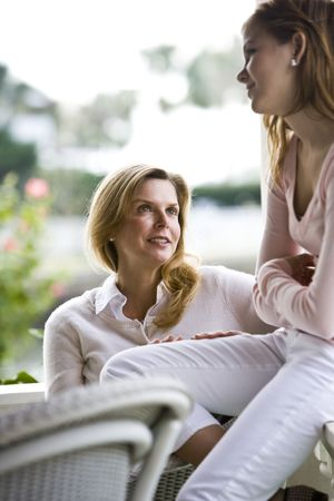 Mother and teen girl having conversation outdoors photo