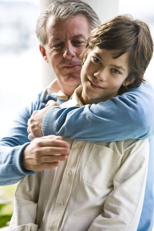 Closeup of father embracing son outdoors photo