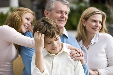 Boy standing in front of affectionate happy family photo