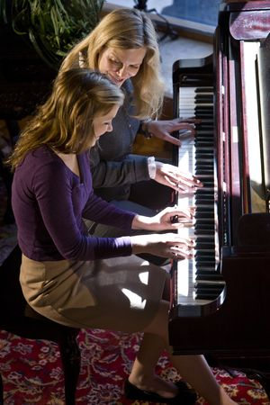 High angle view of mother and teenage daughter playing the piano together photo