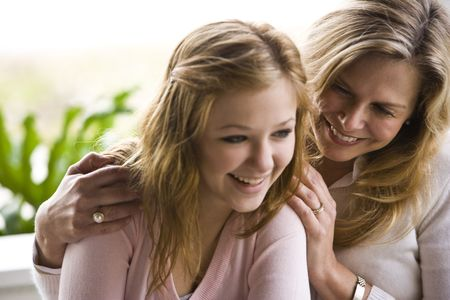 Mature woman and teen daughter laughing together