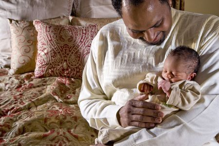 fourties: African American father holding week-old newborn baby