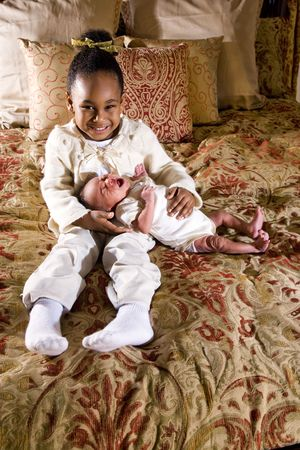 Four year old African American girl holding newborn baby brother photo