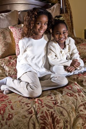 Ten and four year old African American sisters sitting side by side on a bed photo