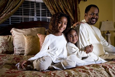 African American father with two little daughters sitting together in bedroom photo