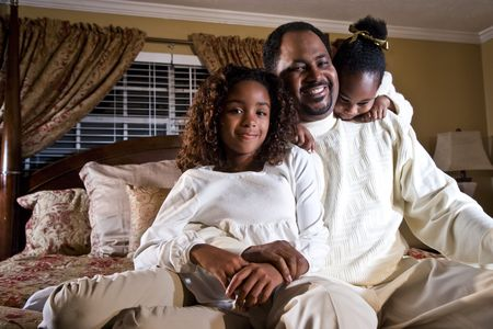 African American father with ten and four year old daughters sitting together in bedroom photo