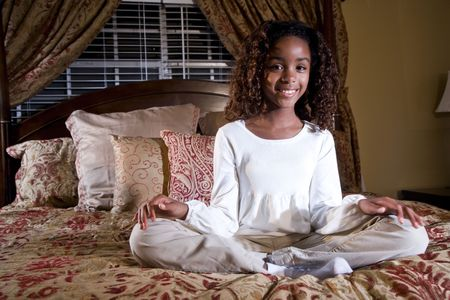 bedspread: Pretty 10 year old African American girl sitting on bed