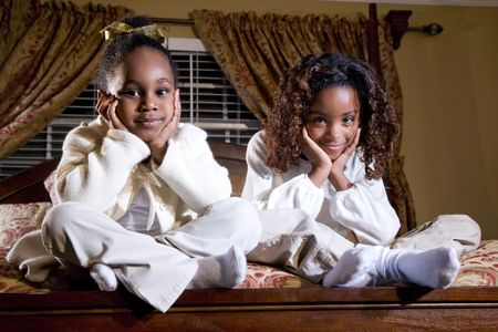 Two cute little African American sisters sitting on a bed photo