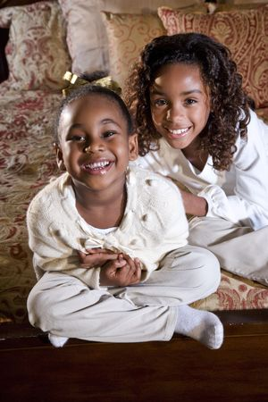 four year old: Ten and four year old African American sisters with happy smiles Stock Photo
