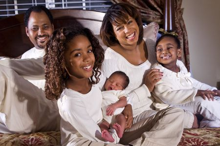Happy African American family with newborn held by big sister photo