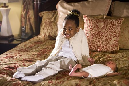 Grinning four year old African American girl sitting next to newborn sibling Stock fotó
