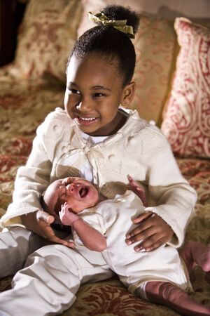 Grinning four year old African American girl holding crying newborn sibling photo
