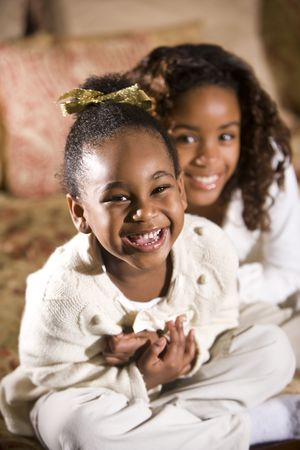 Happy four and ten year old African American sisters sitting together in bedroom photo