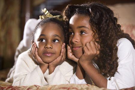 Happy vier tot tien jaar oude African American zusters zitten in de slaap kamer Stockfoto