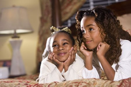 Two happy African American sisters sitting together in bedroom photo