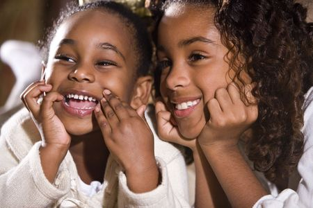 american children: Close up of African American ten and four year old sisters grinning Stock Photo