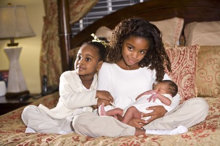 Ten and four year old African American sisters holding their newborn sibling photo