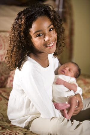 Ten year old African American girl holding her newborn little brother photo