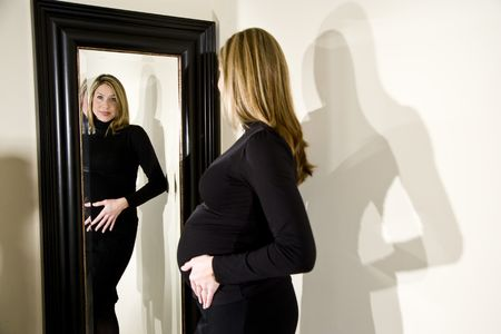with reflection: Pregnant woman admiring her shape in a mirror