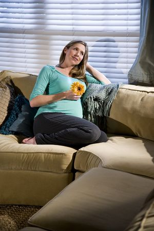 wistful: Wistful pregnant woman relaxing on sofa Stock Photo