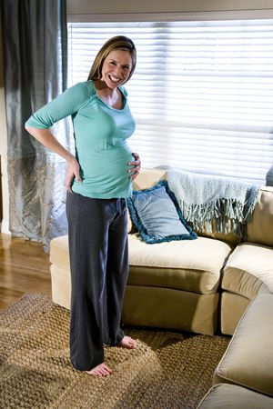 Happy pregnant woman standing in living room photo