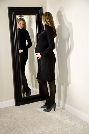 woman mirror: Pregnant woman admiring her shape in a full-length mirror