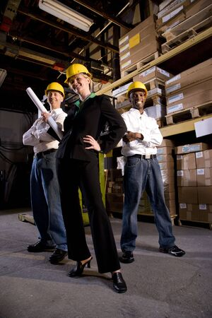 three shelves: Multi-ethnic workers with female boss in storage warehouse
