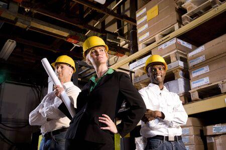 Arbeitnehmer, Bauarbeiter, Vorarbeiter, hard Hats, Crew, Pläne, 40er Jahre, 20er Jahre, Mitte erwachsen frau, Mitte erwachsenen Mann, junger Mann, hand auf Hüfte, Armen, posing, Grundrisse, Warehouse, Abstellraum, Regale, Kisten, Paletten, zuversichtlich, das Vertrauen, weiblich, männlich, Männer,  Standard-Bild - 6329230