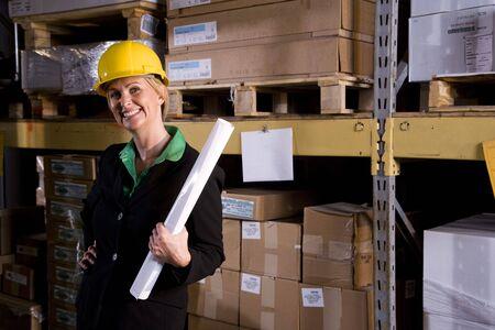 Female office worker standing in storage warehouse Zdjęcie Seryjne