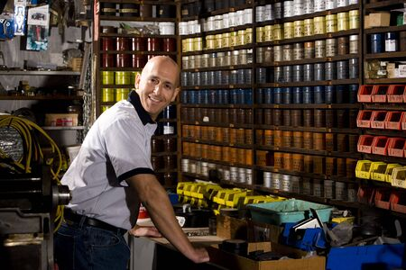mature business man: Man standing in front of colored inks in print shop