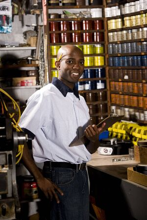 taking inventory: Man standing in front of colored inks in print shop