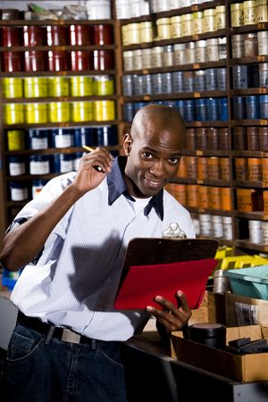 taking inventory: African American worker standing in front of colored inks in print shop