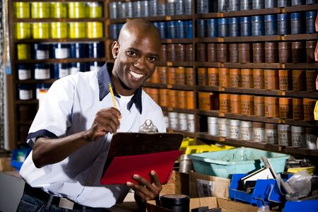 Man standing in front of colored inks in print shop photo