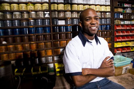 african business people: Man sitting in front of colored inks in print shop Stock Photo