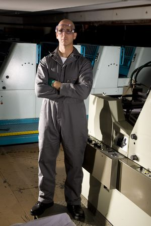 Man in print shop standing by printing press photo