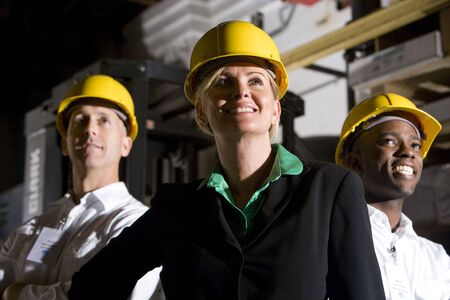 Office workers in storage warehouse wearing hard hats photo