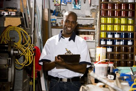 taking inventory: Portrait of African American man holding a clipboard in printing company
