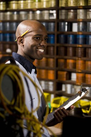 Young African American male worker working in print shop by shelves of ink photo