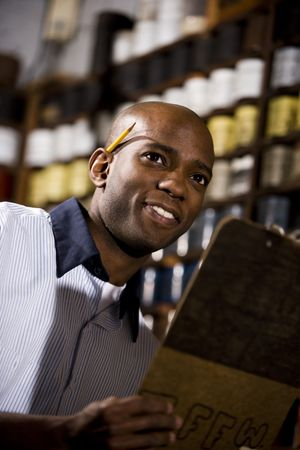 taking inventory: Young African American male worker working in print shop by shelves of ink