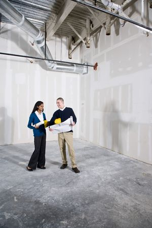 new construction renovation: Multi-ethnic man and woman in empty commercial office space ready for buildout Stock Photo