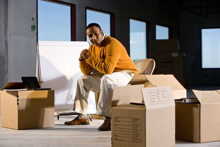 fourties: African American man surrounded by boxes in office space