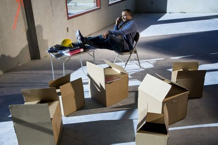 out of a box: African American man surrounded by boxes in empty unfinished office space Stock Photo