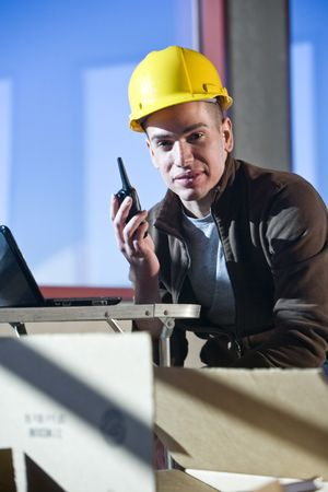 walkie: Closeup of male construction worker holding walkie talkie
