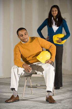 Multi-ethnic man and woman in empty commercial office space ready for buildout photo