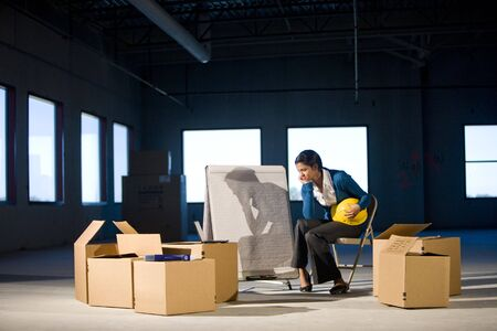 empty: Young woman in empty office space with moving boxes