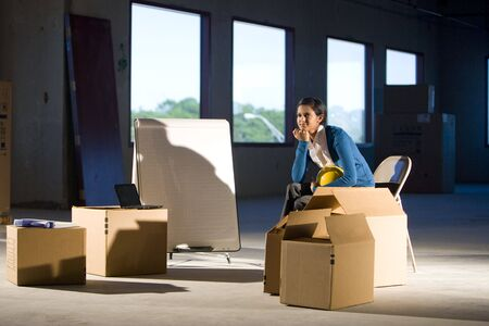 out of a box: Young woman in empty office space with moving boxes