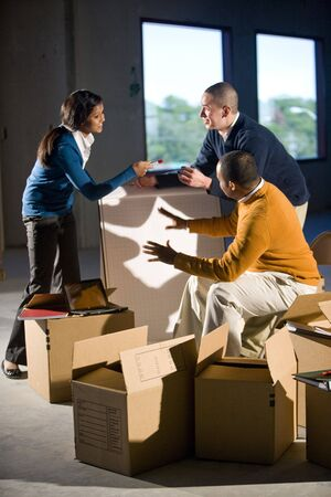new office space: Multi-ethnic businesspeople preparing new office space Stock Photo