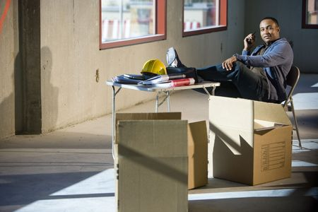 befejezetlen: Worker in unfinished office space with feet up on folding table